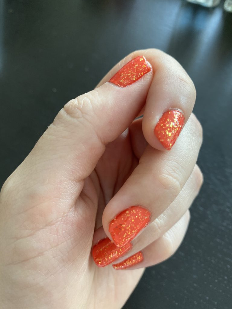 my hand, with orange glitter nails
