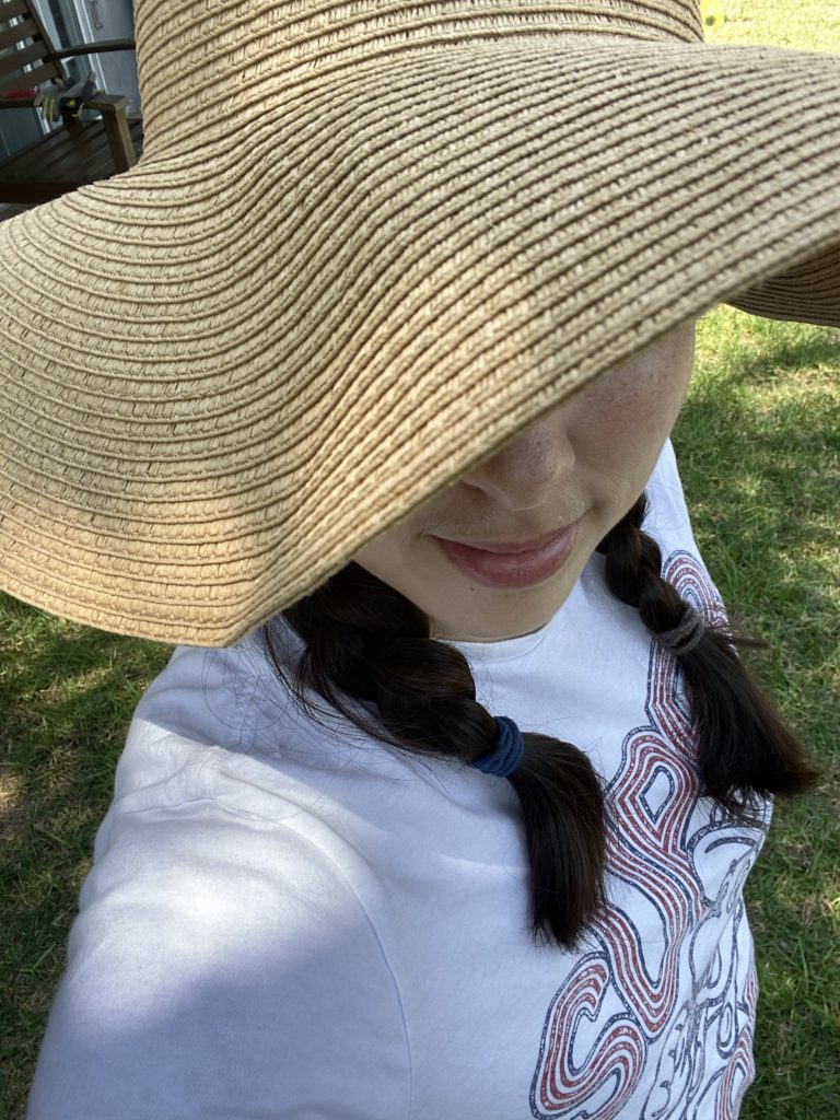 me wearing a hat, showing the bottom of two braids