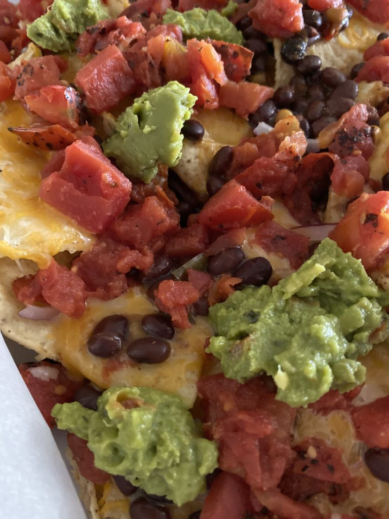 nachos with beans, tomatoes, and guac