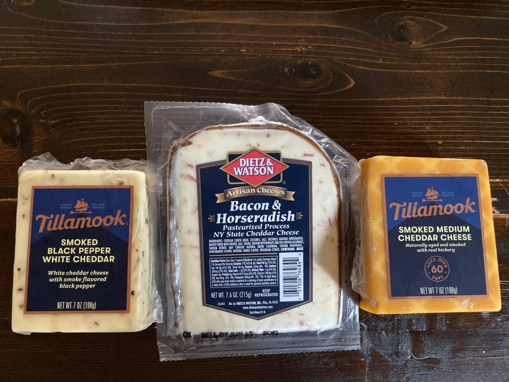 three types of cheese: smoked black pepper white cheddar, bacon and horseradish cheddar, and smoked medium cheddar