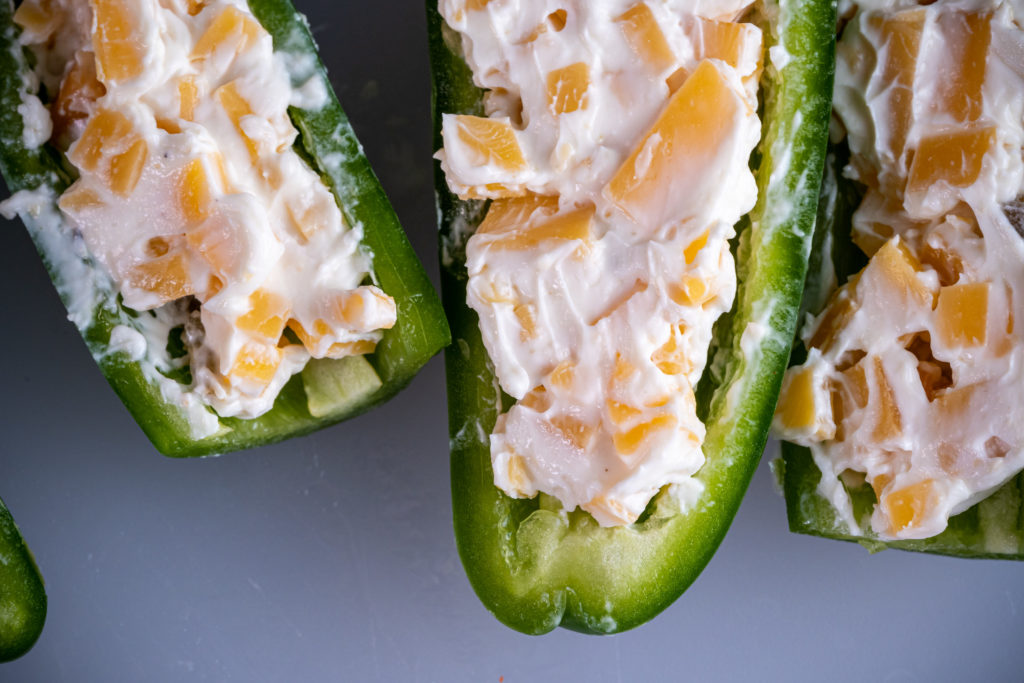 uncooked jalapenos stuffed with cream cheese and cheddar cubes