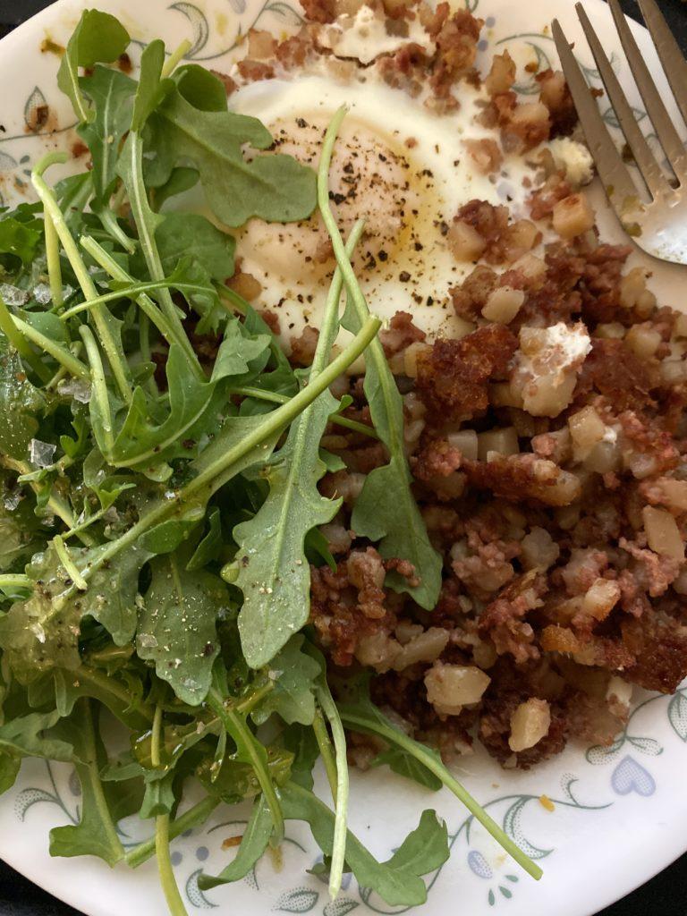corned beef hash, fried egg, and arugula salad