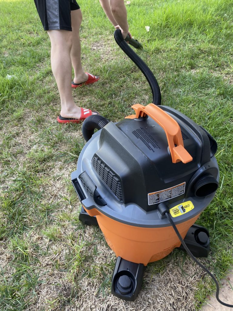 shop vac on a lawn, with Son vacuuming something