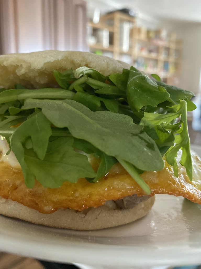 english muffin with arugula, frico egg, and sausage