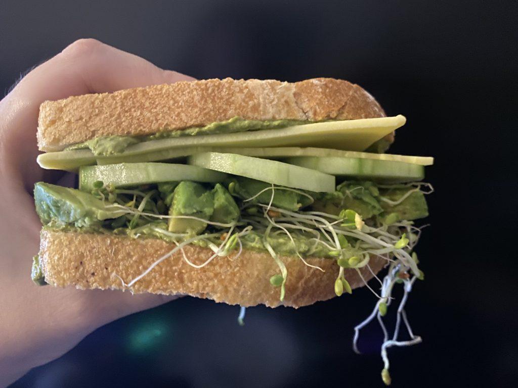 my hand holding a green goddess sandwich