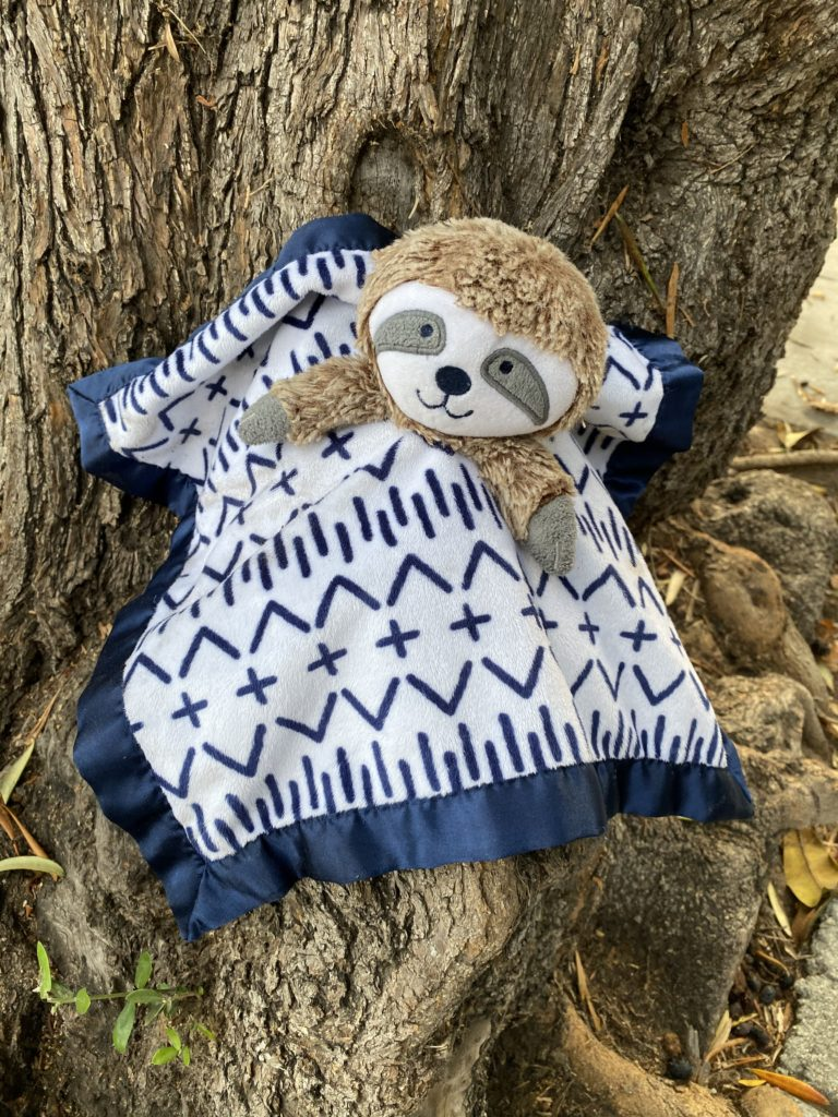 a sloth toy in a blanket